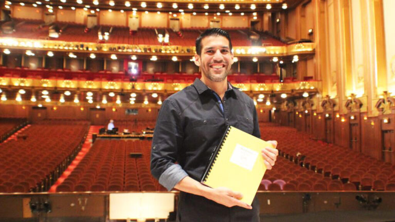 """Composer Jimmy López proudly displays the completed piano-vocal score of his first opera, """"Bel Canto,"""" on the stage of the Ardis Krainik Theatre in the Civic Opera House, home of Lyric Opera of Chicago."""