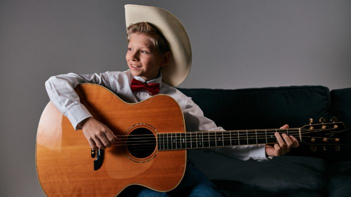 Color photo of Mason Ramsey viral yodeling sensation with guitar