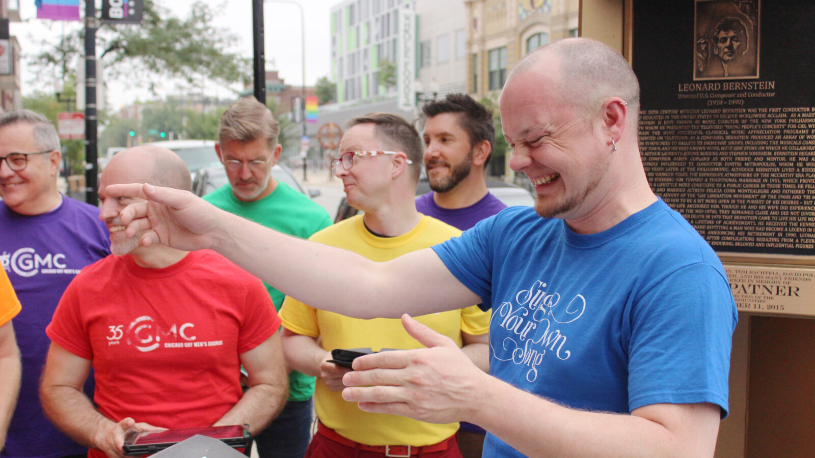 Members of the Chicago Gay Men's Chorus and Artistic Director Jimmy Morehead share a moment at the Leonard Bernstein memorial plaque on the Legacy Walk.