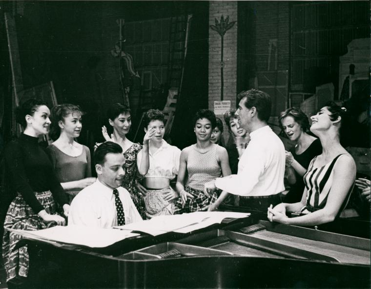 Stephen Sondheim on piano and Leonard Bernstein standing amongst female singers rehearsing for West Side Story