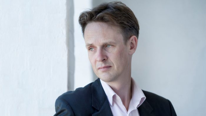 Portrait of Ian Bostridge looking over right shoulder, very white back ground.
