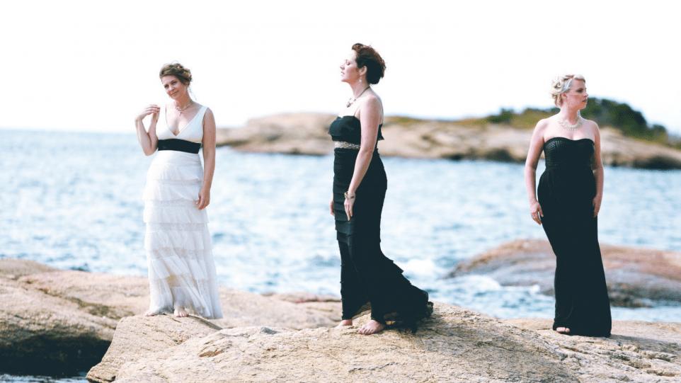 Three singers dressed elegantly on a beach