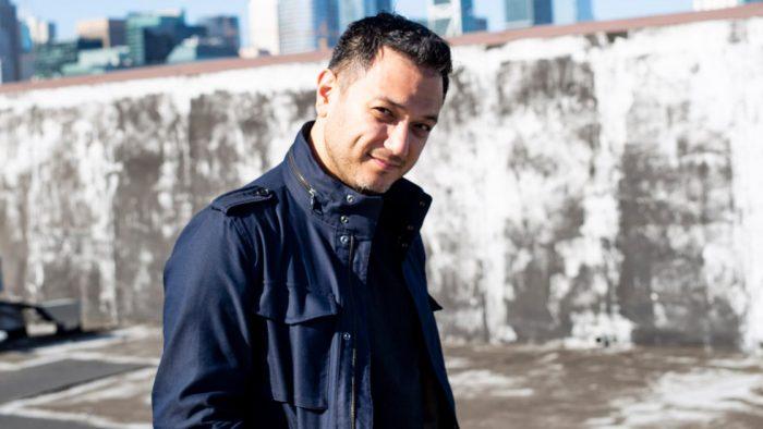 Portrait of Nicholas Phan in urban landscape wearing a black coat
