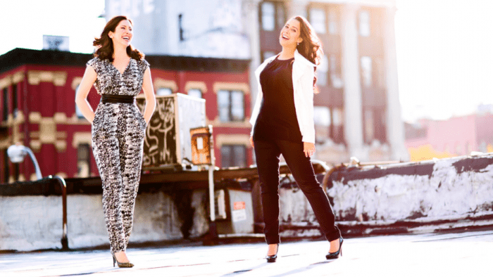 Camille Zamora (in a snake print jumpsuit) and Monica Yunus (in a black and white pantsuit) portrait in urban setting.