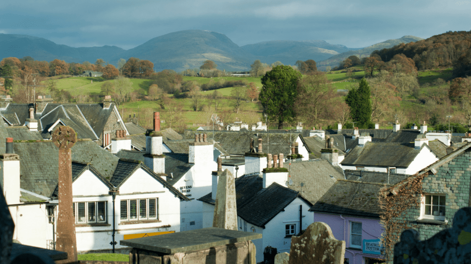 A view of the roof tops of the village of Hawkshead across to the Cumbrian hills in the distance including red screes and ill bell