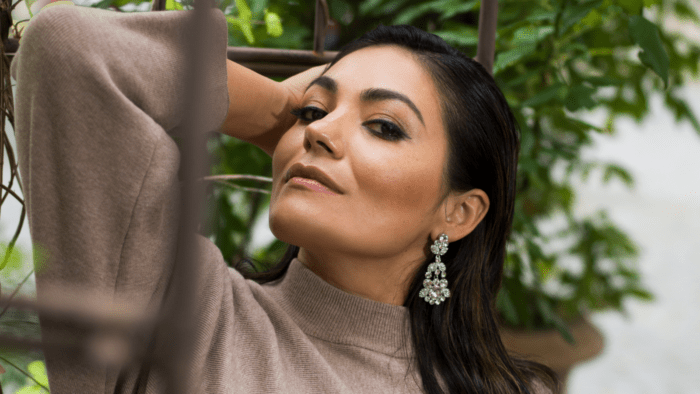 Portrait of Ailyn Pérez in profile, beige sweater dress, dramatic earrings