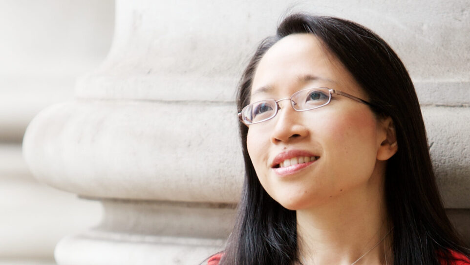 Portrait of Eugenia Cheng in front of bright stone building, looking into distance.